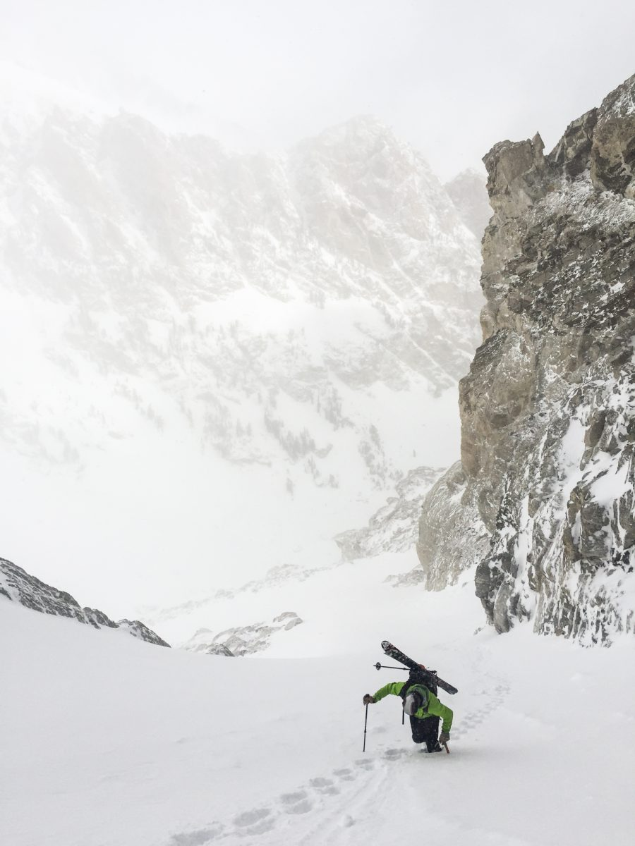 Climbing a steep boot pack with skis in the Tetons